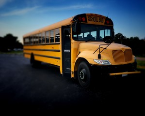 Yellow public school bus front right high angle with blurred background