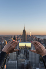 Woman taking a picture of New York skyline.