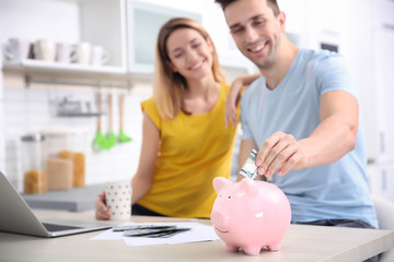 Young couple with piggy bank at home