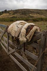 A saddle on a fence