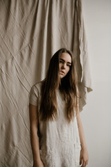 young woman standing in front of wrinkled cloth wearing simple cloth dress