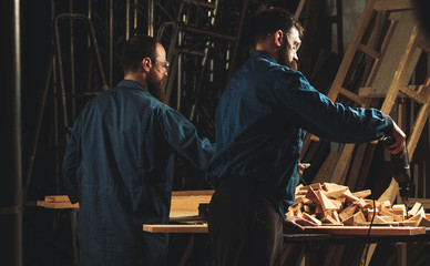 Two carpenters working in workshop/sawmil with wood.