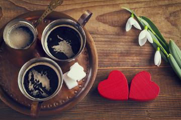 Valentines love concept for two. Turkish coffee in copper set and two red hearts on wooden background. Vintage effect.