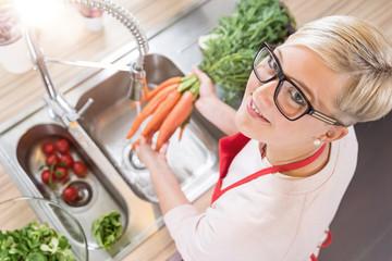 Hübsche junge Frau lächelt in die Kamera, während sie Karotten wäscht