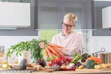 Junge Frau freut sich aufs Kochen, des frisch gekauften Gemüses