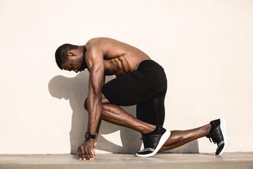 Black athlete sprinting on the street.