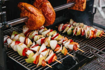 Skewers with pieces of sausages, onions, peppers are cooked on a grate on coals. Rest and eating outdoors. On top of the large pieces of meat.