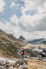 Woman standing on the rock enjoying mountain landscape