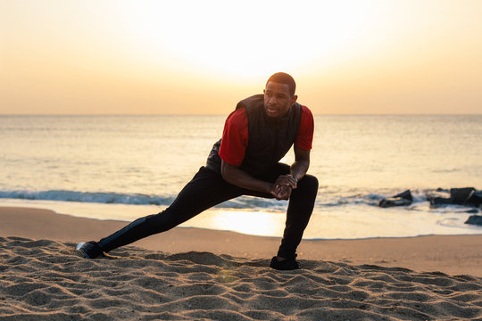 Young black athlete stretching on the beach at sunrise.