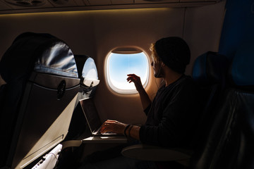 Young man working on a laptop while traveling in an Airplane