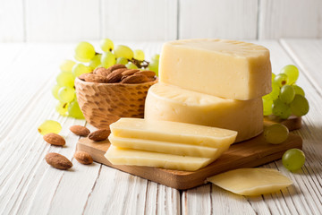 Pieces of cheese on wooden board with almonds and green grape on white wooden background.