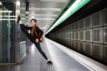 Young woman doing stretch exercises on the subway platform