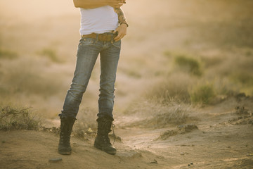 detail of legs of sexy woman in jeans and boots in the desert