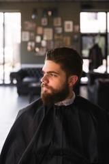 Bearded young man sitting on barber chiar in barbershop