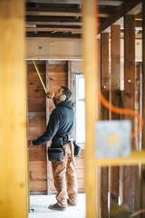 Carpenter man working on jobsite measuring