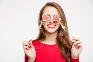 beautiful brunette girl closed her eyes with two hearts of souvenirs. Valentine's day concept. On white background. Place for text