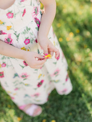 Girl in Floral Dress Holding a Flower