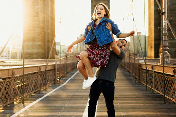 Beautiful young man and woman pose on the Brooklyn Bridge in the rays of morning sun