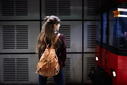 Young woman with bagpack waiting for the subway