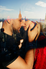 Reflection of tender hugging couple in a window with great view on the New York city