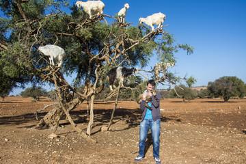Junger Mann hält Ziege in den Armen vor  einem Arganbaum