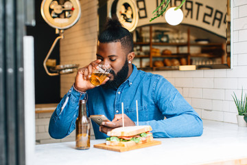 African american man using smartphone in a pastrami bar.