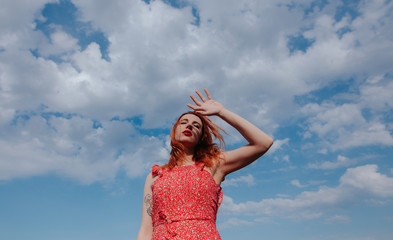 ginger woman on  red dress protecting her face from the sun