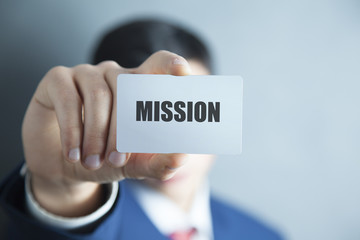 mission text on card on man hand