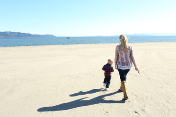 Mother and child walking on the beach on a sunny day.