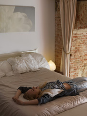 Tired woman lying on a bed