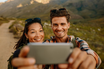 Young man and woman taking selfie on country hike