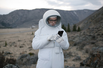 Cosmonaut standing with a phone