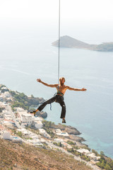 Male rock climber with outstretched arms hanging on rope