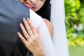 The bride hugged the groom.