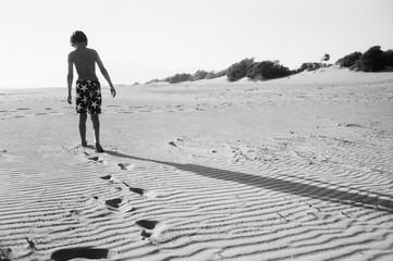 Rear view of boy leaving footprints in sand