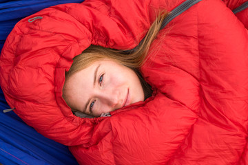Young woman smiling while resting in in red sleeping bag