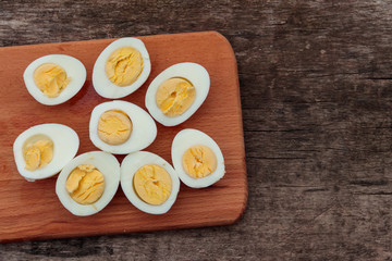 Boiled eggs on cutting board on wooden table