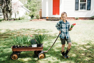 boy with wagon full of flowers and plants