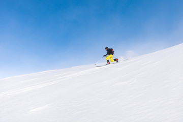 Man skiing telemark style on steep slope on a bright day