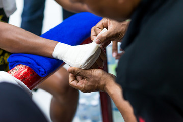 Muay Thai or Thai boxing fighter putting bandage on the hands preparing to fight