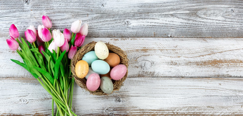 Bouquet of tulips and colorful eggs for Easter on white wood
