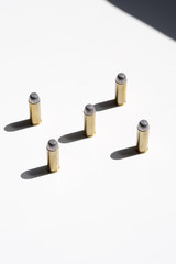 five brass bullets on a white background