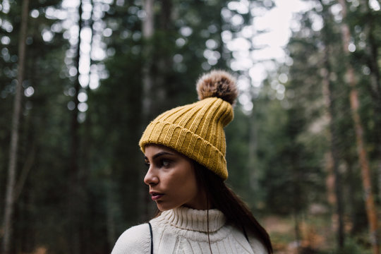 Portrait of a beautiful young woman in the forest wearing a beanie