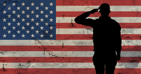 Silhouette soldier against background an old stone wall with flag of the USA