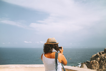 Brunette woman taking pictures at the sea