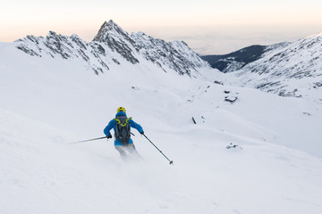 Back view of male skier freeriding off piste