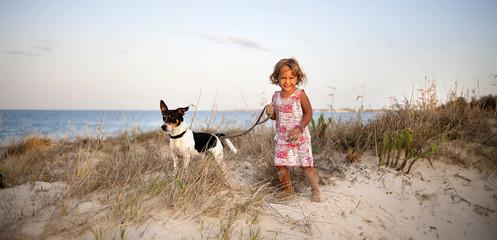little girl with a dog on the beach