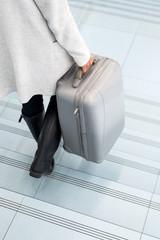 Crop female holding luggage