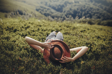 stylish traveler woman in hat lying on grass and relaxing in mountains. hipster girl on top of mountain, resting, hat on her face. space for text. atmospheric moment. wanderlust and travel concept.