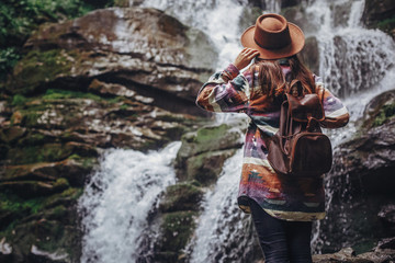 stylish traveler girl in hat looking at waterfall, exploring woods. hipster woman with backpack travelling, holding hat at river in forest. space for text. wanderlust and travel concept